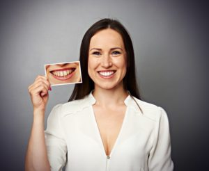 Smiling woman holds photo pf before visiting her North Dallas cosmetic dentist